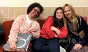 Photo of 3 women sitting in a hallway on college campus, smiling. Left to right: woman in pink sweater, short dark curly hair and glasses, holding a binder; woman in black shirt with red sweater, arms and legs crossed; woman with long blond hair, leaning on woman in red sweater