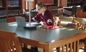 Girl leaning over books at a table in a library