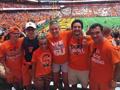 a group of Syracuse University students, all dressed in SU orange, at a football game.