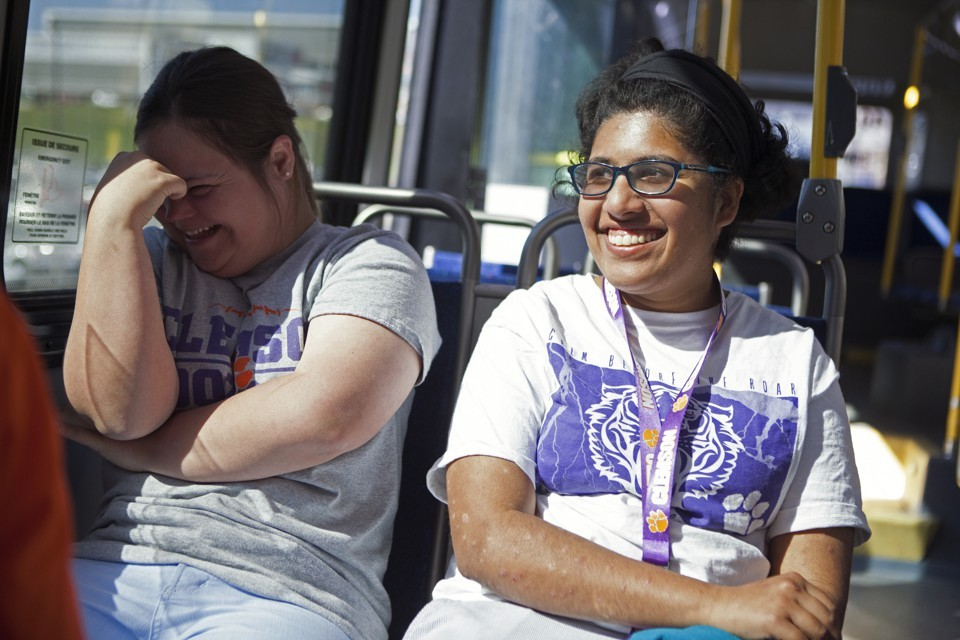 Two young women laughing on a bus.