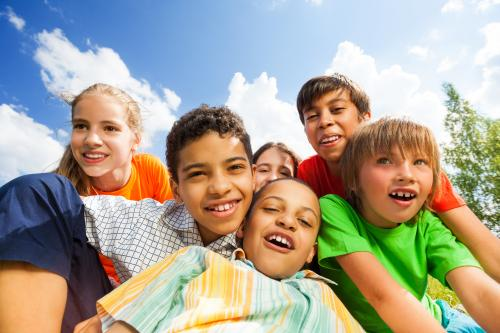group of 6 elementary-aged kids crowded together, smiling, with blue sky in the background