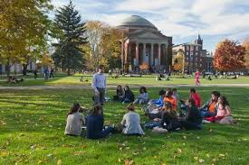 college campus with students sitting on lawn